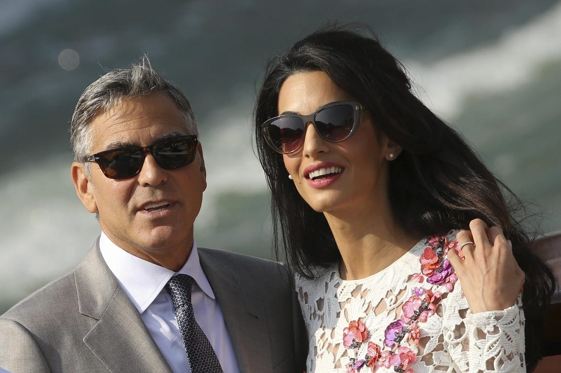 U.S. actor George Clooney and his wife Amal Alamuddin travel on a water taxi at the Grand Canal in Venice September 28, 2014. The world's most famous bachelor broke a vow to remain single on Saturday and married human rights lawyer Alamuddin during a weekend of lavish celebrations in Venice. The Italian city of gondolas and palazzi looked like Hollywood on the Adriatic as A-list guests cruised between luxury hotels for the extravaganza, billed as the party of the year even as details were kept largely secret. REUTERS/Alessandro Bianchi (ITALY - Tags: ENTERTAINMENT PROFILE)